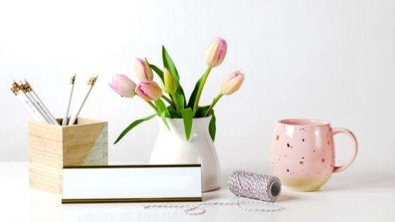 Pink mug next to pink tulips and pencils