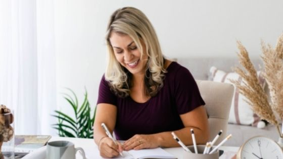 Woman smiling sitting at her desk and writing