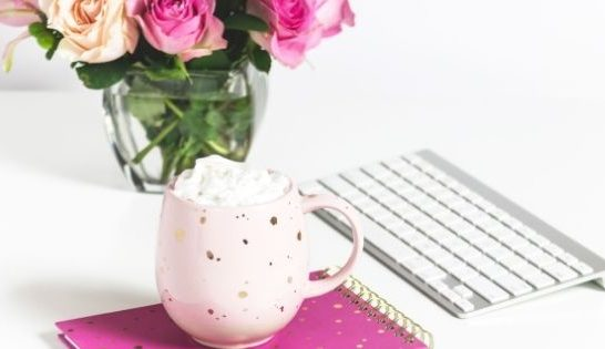Mug on pink notebook next to flowers and computer keyboard
