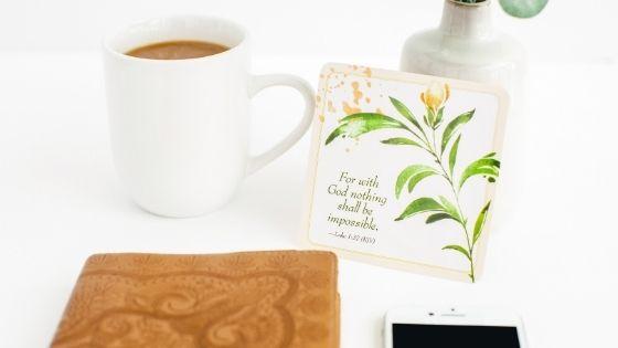 Coffee mug next to Bible and Scripture card