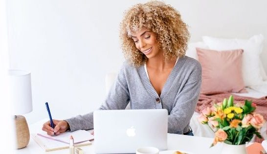 Woman writing in notebook smiling overcoming fear in life
