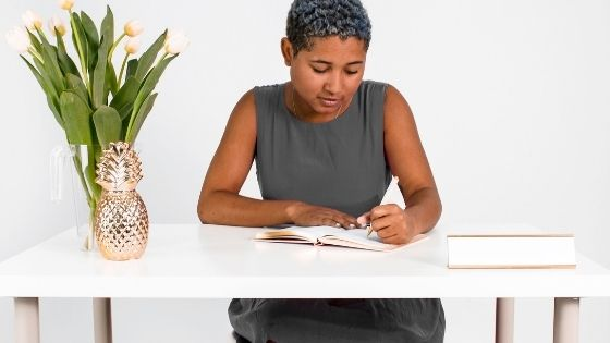 African American girl sitting and writing in her notebook at a desk