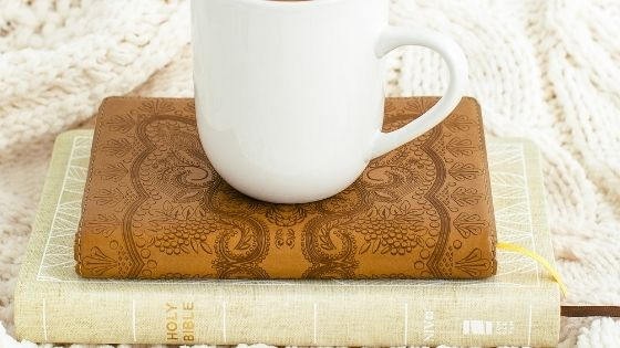 Cup of coffee on top of Bible and Brown Journal