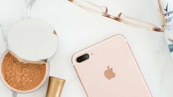 I-Phone next to make-up and glasses